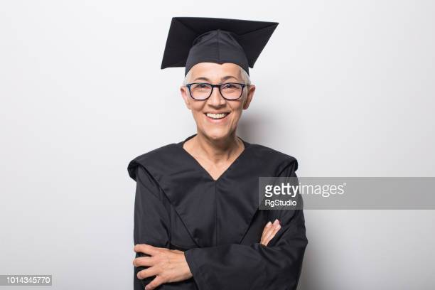 Smiling woman with hands clasped wearing graduation gown and eyeglasses