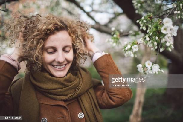 smiling woman with hands in hair at park - bortes imagens e fotografias de stock