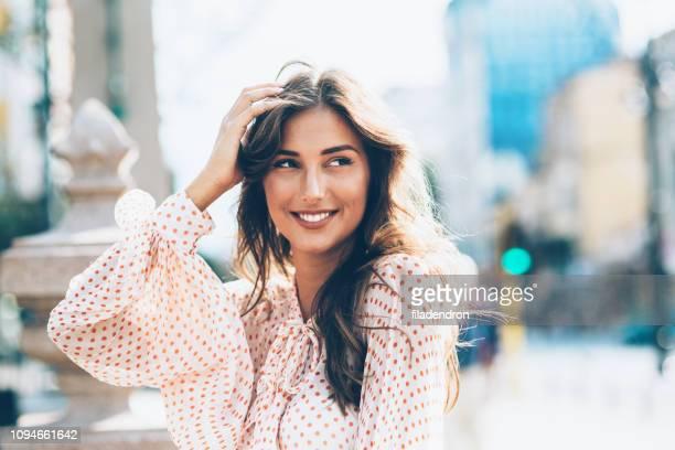 lächelnde frau mit händen in haar - welliges haar stock-fotos und bilder