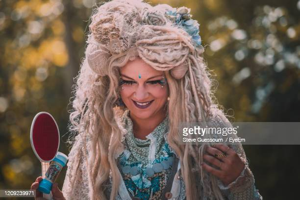 smiling woman with headdress and make-up looking down - steve guessoum stockfoto's en -beelden