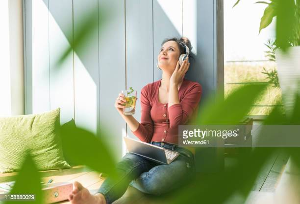smiling woman with headphones and laptop sitting at the window at home - differential focus stock pictures, royalty-free photos & images