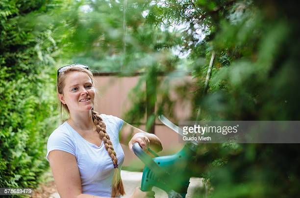 Smiling woman with hedge trimmer.