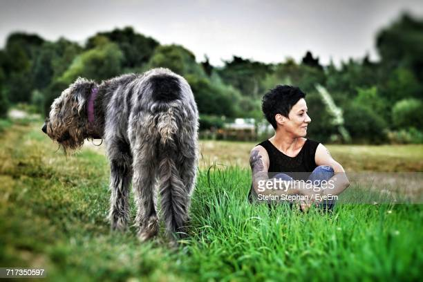 Smiling Woman With Irish Wolfhound Sitting On Grassy Field