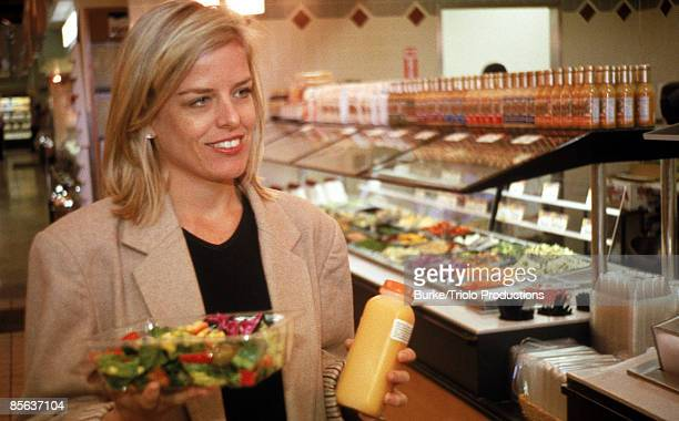 Smiling woman with juice and salad