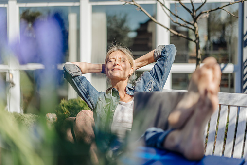 Smiling woman with laptop relaxing on garden bench - gettyimageskorea