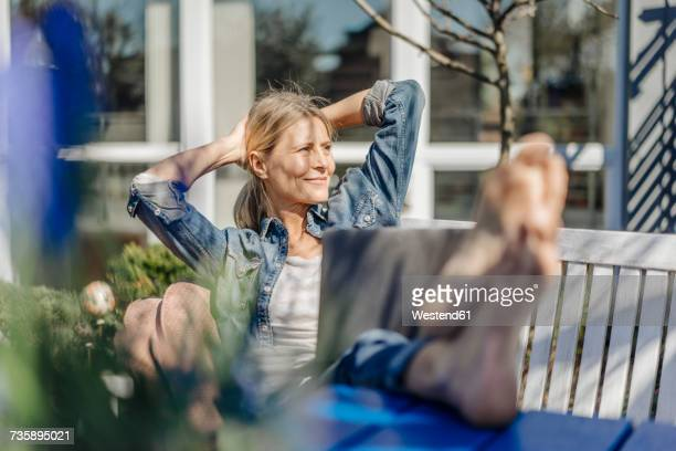smiling woman with laptop relaxing on garden bench - gelassene person stock-fotos und bilder
