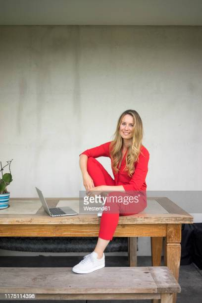 smiling woman with laptop sitting on wooden table at home - jumpsuit stock pictures, royalty-free photos & images