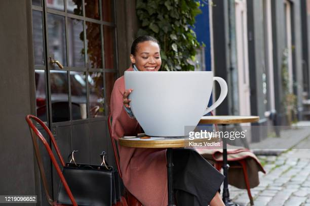 smiling woman with large coffee cup sitting at sidewalk cafe - sac à main surdimensionné photos et images de collection