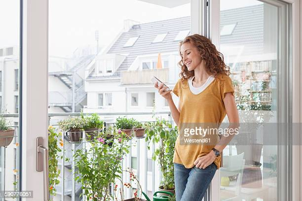 Smiling woman with leaning against balcony door looking on cell phone