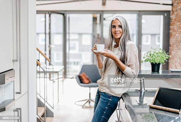 smiling woman with long grey hair drinking coffee - capelli grigi foto e immagini stock