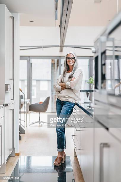 smiling woman with long grey hair in kitchen - 45 49 years stock pictures, royalty-free photos & images