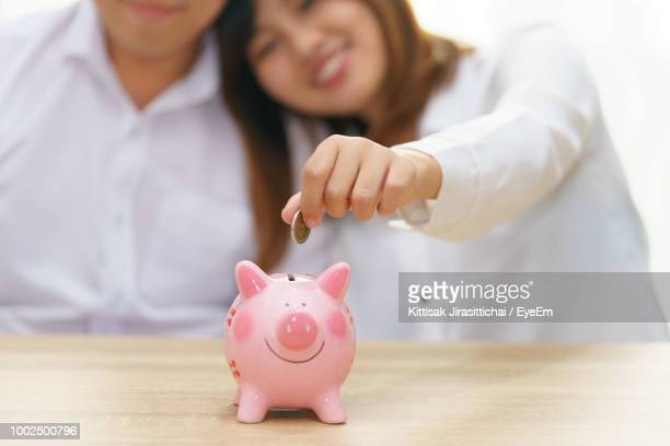 Smiling Woman With Man Putting Coin In Piggy Bank