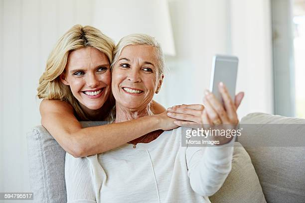 Smiling woman with mother talking selfie at home