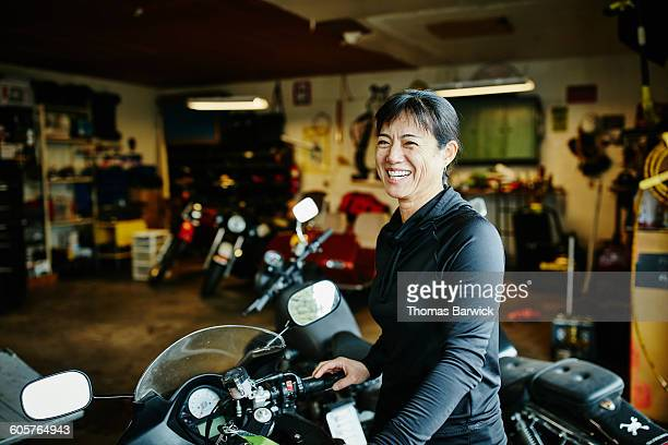 Smiling woman with motorcycle in garage