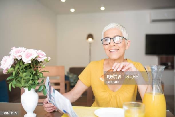 新聞を女性と彼女の手でクロワッサンを笑顔
