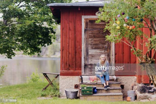 Smiling woman with organic vegetable sitting outside wooden cottage
