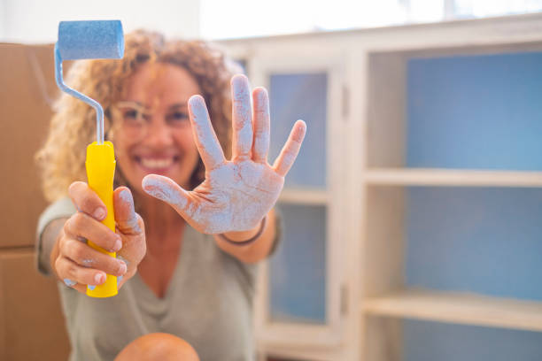 Smiling woman with paint roller and blue paint on hand at home