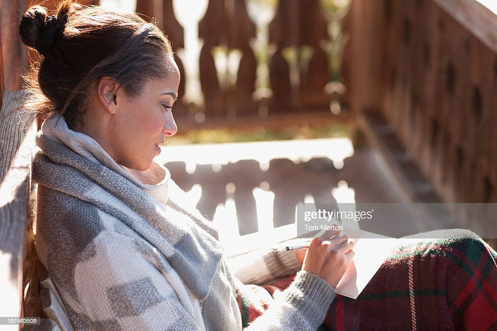 Smiling woman with paper and pen on cabin porch : Stock Photo