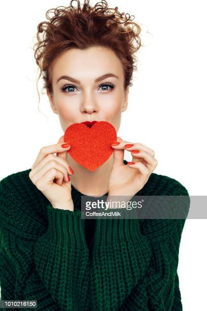 smiling woman with paper heart - heart month stock photos and pictures