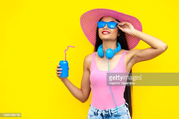 smiling woman with pink hat holding blue can - multi colored hat stock pictures, royalty-free photos & images