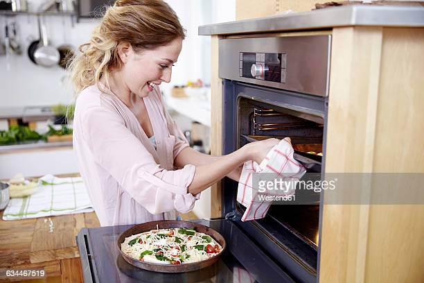 Smiling woman with pizza on baking pan at oven