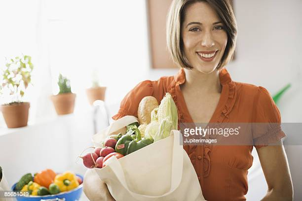 Smiling woman with produce in canvas bag