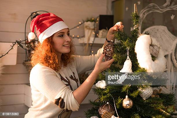 Smiling woman with Santa's hat decorating a Christmas tree.