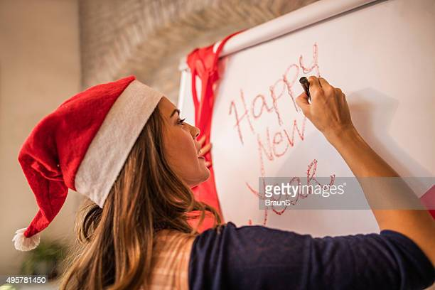 Smiling woman with Santa's hat writing on whiteboard at office.