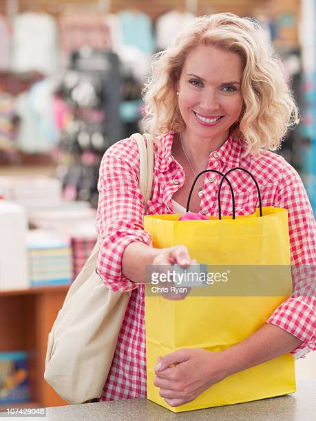 Smiling woman with shopping bag handing credit card