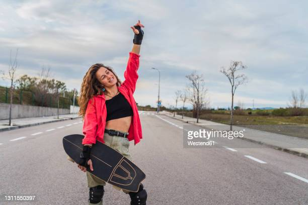 smiling woman with skateboard gesturing horn sign while standing on road against sky - fingerless gloves stock pictures, royalty-free photos & images