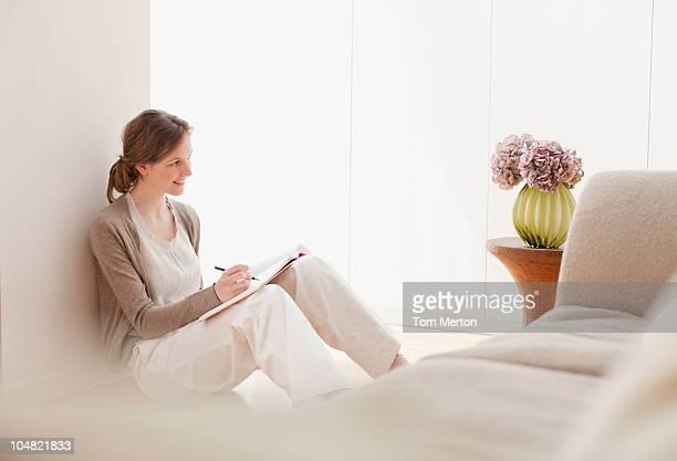 Femme souriante avec carnet à croquis examinant des fleurs dans un vase