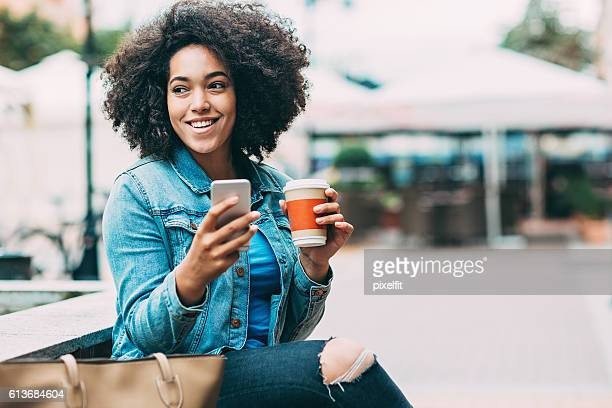 smiling woman with smart phone and coffee cup - donna creola foto e immagini stock