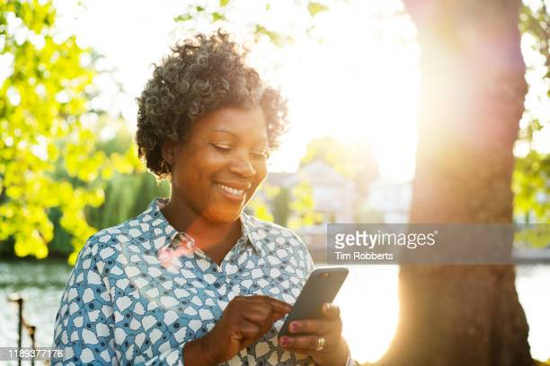 smiling woman with smart phone outside - black ethnicity stock pictures, royalty-free photos & images