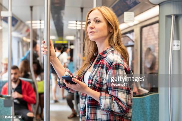 smiling woman with smartphone on the subway, berlin, germany - bahnreisender stock-fotos und bilder