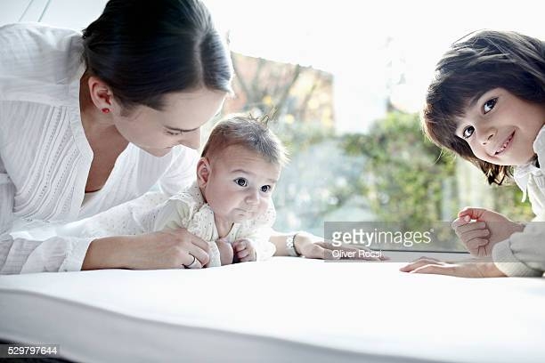 smiling woman with son (6-7) and baby daughter (6-11 months) lying by window - 6 11 months stock pictures, royalty-free photos & images