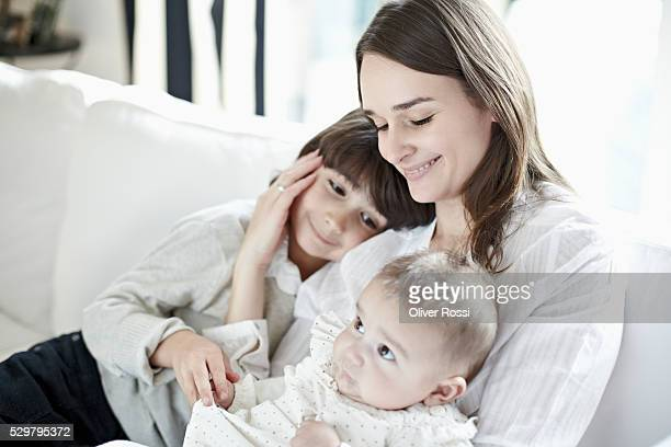 smiling woman with son (6-7) and baby daughter (6-11 months) sitting on sofa - 6 11 months stock pictures, royalty-free photos & images