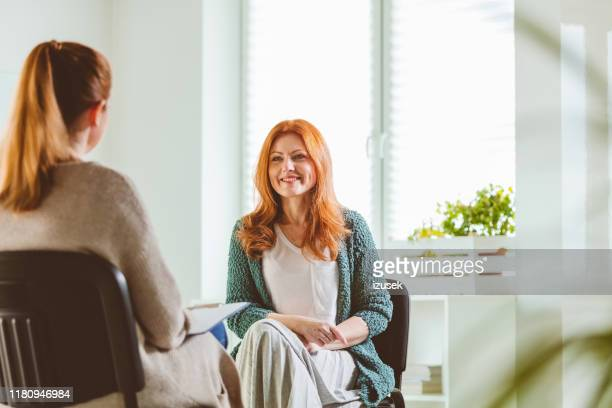 smiling woman with therapist at community center - alternative medicine stock pictures, royalty-free photos & images