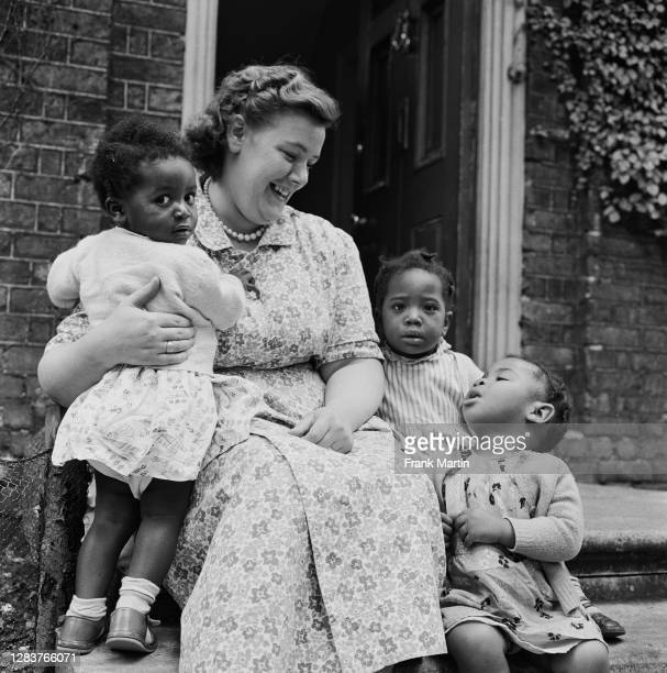 Smiling woman with three little girls at a day nursery in the Notting Hill area of west London, circa 1958.