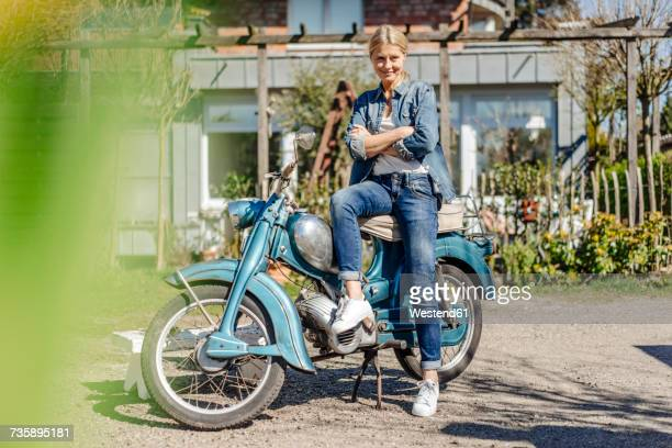 Smiling woman with vintage motorcycle