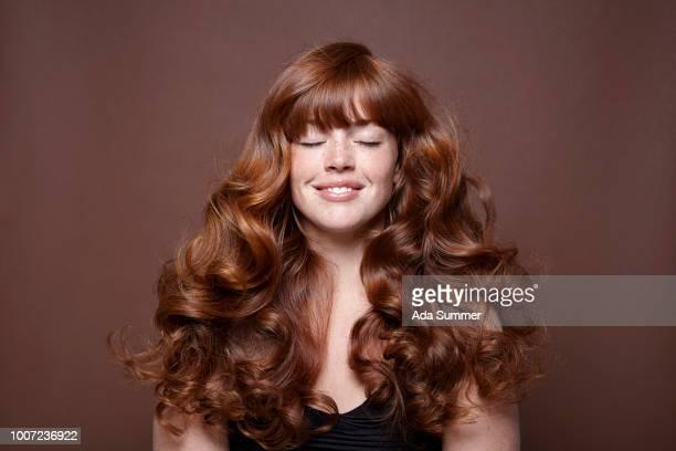smiling woman with windblown red long hair - haar stock-fotos und bilder