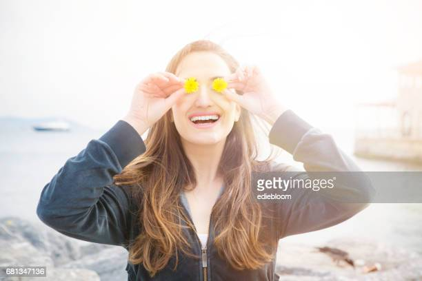Smiling woman with yellow dandelions in front of her eyes