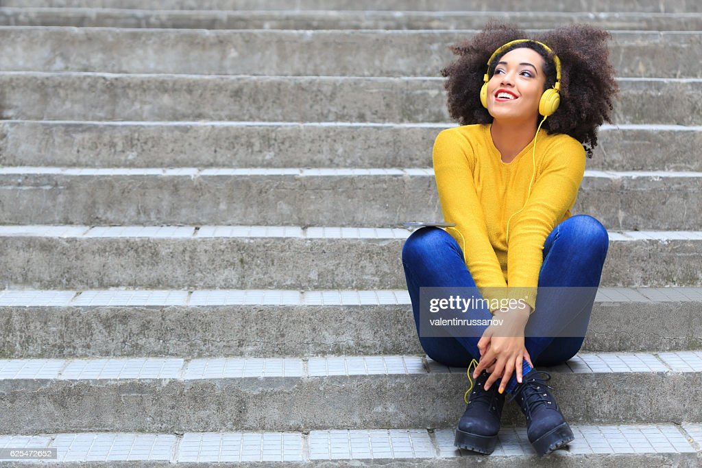 Smiling woman with yellow headphones sitting on stairs : Stock Photo