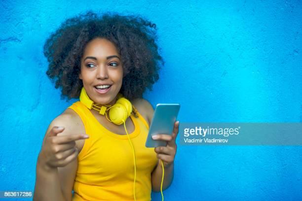 Femme souriante avec gilet jaune et casque d'écoute de musique