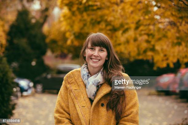 Smiling woman with yellow wool coat in autumny nature