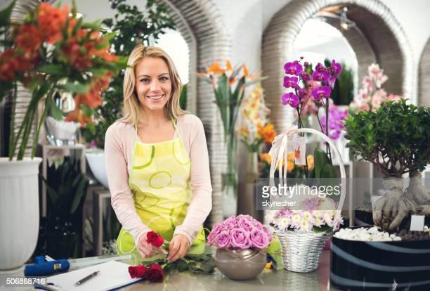Mulher sorridente a trabalhar em loja de flores e olhando para a câmara.