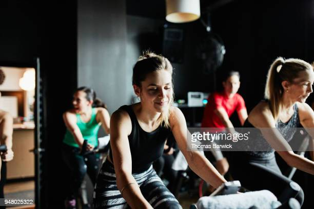 Smiling woman working out on stationary bike during fitness class in cycling studio