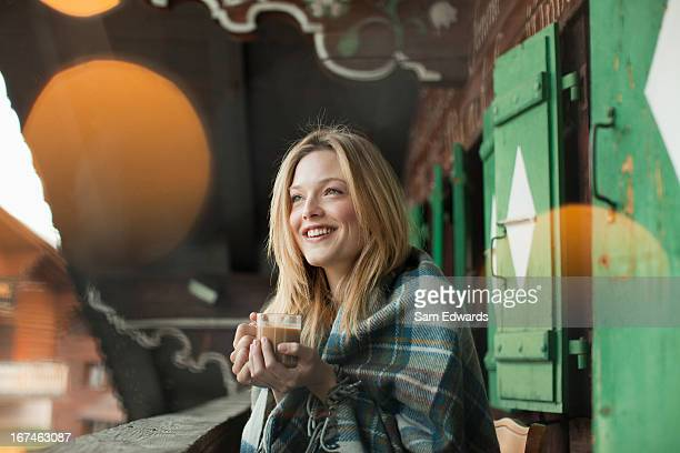smiling woman wrapped in a blanket and drinking coffee on cabin porch - hot blonde woman stock pictures, royalty-free photos & images