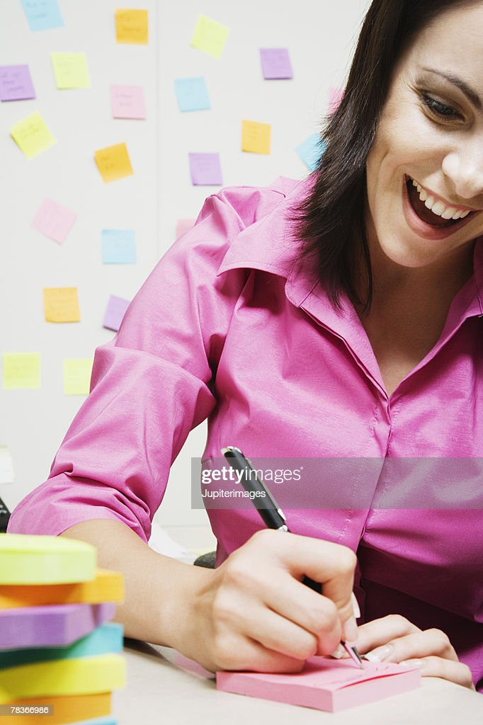 Smiling woman writing on sticky note in office : Stock Photo