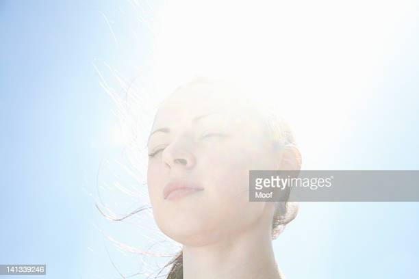 smiling womans face against blue sky - zen like stock pictures, royalty-free photos & images