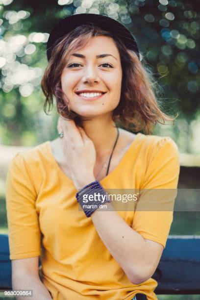 smiling woman's portrait - yellow hat stock pictures, royalty-free photos & images